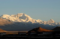 Dusk, sunset in front of the snowy mountains of the Cho Oyo, 8112 m, in the Tingri plateau, with Tibetan buildings of the village of Old Tingri, Tibet...
