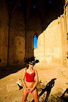 Girl with feather mask standing in gothic ruins