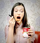 Woman eating cat food