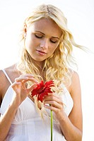 Young woman holding a red flower