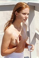 Naked young woman applying suncream on her chest, outdoors