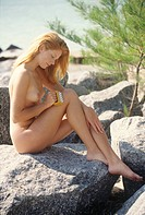 Naked young woman massaging her thigh, outdoors
