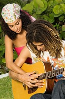 Man teaching a woman how to play a guitar