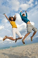 Teenage boy with a girl jumping on the beach