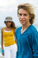 Teenage boy standing with a girl on the beach (thumbnail)