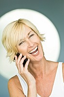 Woman talking on a mobile phone and laughing (thumbnail)