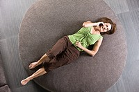Woman lying on a round sofa and talking on a mobile phone