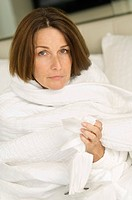 Portrait of a woman wrapped in a blanket and holding tissue paper