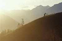 Mountain biker pushing bikeup steep slope in evening Banff NP CANADA Alberta