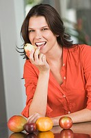 Woman eating a pear and smiling