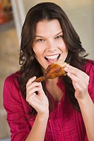 Woman eating chicken (thumbnail)