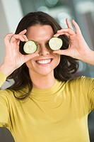 Woman holding cucumber slices in front of her eyes