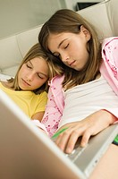 Two girls sleeping with a laptop on their laps