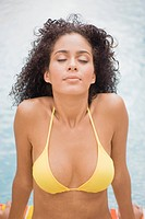 Woman sitting at the poolside with her eyes closed (thumbnail)
