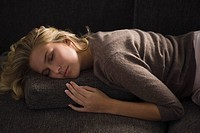 Close_up of a woman napping on a couch