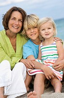 Woman sitting with her grandchildren on the beach