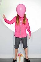 Pink balloon tied with a birthday present in front of a girl's face (thumbnail)