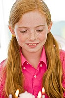 Close-up of a girl looking at a birthday cake (thumbnail)