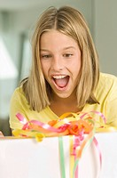 Girl looking at a birthday present with a surprise (thumbnail)