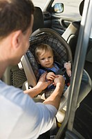 Man fastening his son on a baby seat in a car