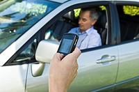 Person's hand text messaging and a man sitting in a car in the background