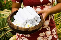 Woman holding rolled towels and flowers in a basket, Bora Bora, Tahiti, French Polynesia