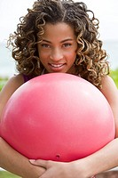Portrait of a girl hugging a ball and smiling (thumbnail)