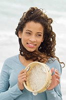 Close_up of a girl playing a tambourine
