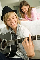 Teenage boy playing a guitar and his sister using a mobile phone behind him