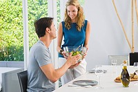 Woman giving a bowl of salad to her husband