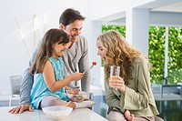 Girl feeding fruit salad to her mother