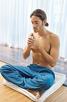 Man smelling aromatherapy oil from a bottle