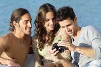 Three friends looking at a digital camera