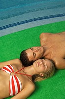 Couple sunbathing at the poolside