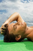 Man sunbathing at the poolside (thumbnail)