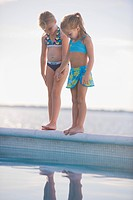 Two girls standing at the poolside
