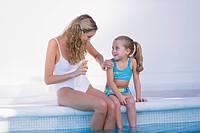 Woman with her daughter sitting at the poolside