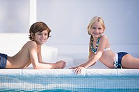 Boy with a girl lying at the poolside and smiling