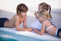 Two girls and a boy at the poolside
