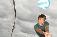 Man playing volleyball on the beach (thumbnail)