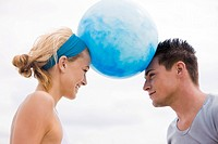 Couple balancing beach ball between their heads (thumbnail)