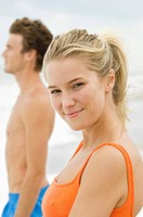 Portrait of a woman standing with a man on the beach (thumbnail)