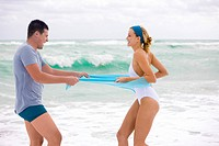 Man pulling sarong of a woman on the beach (thumbnail)
