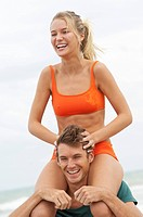 Man carrying a woman on his shoulders on the beach