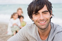 Man smiling with his family behind him on the beach