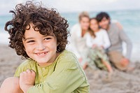 Boy smiling with his family behind him on the beach