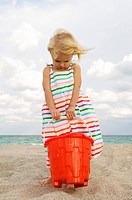 Girl holding a sand pail on the beach
