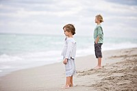 Two boys standing on the beach
