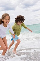 Boy and a girl running on the beach