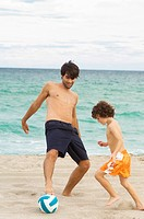 Boy playing soccer with his father on the beach